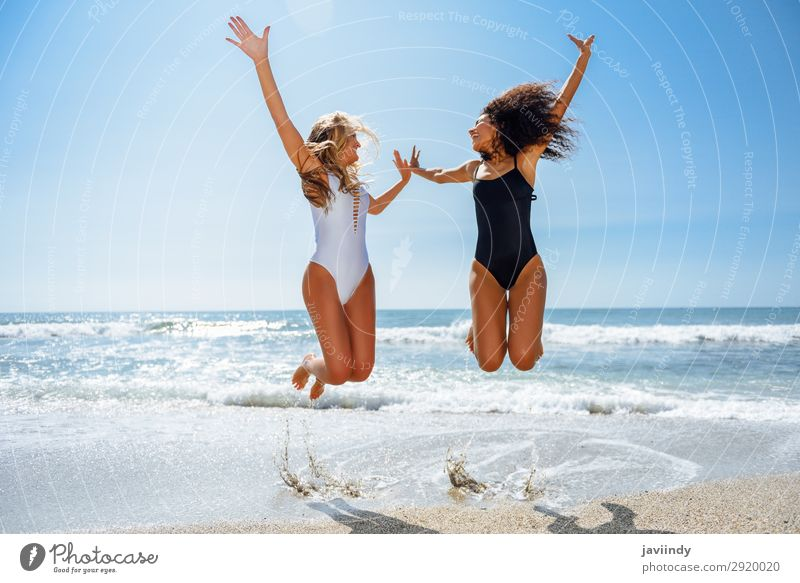 Two funny girls in swimsuit jumping on a tropical beach in summer. Lifestyle Joy Happy Beautiful Body Hair and hairstyles Leisure and hobbies Vacation & Travel