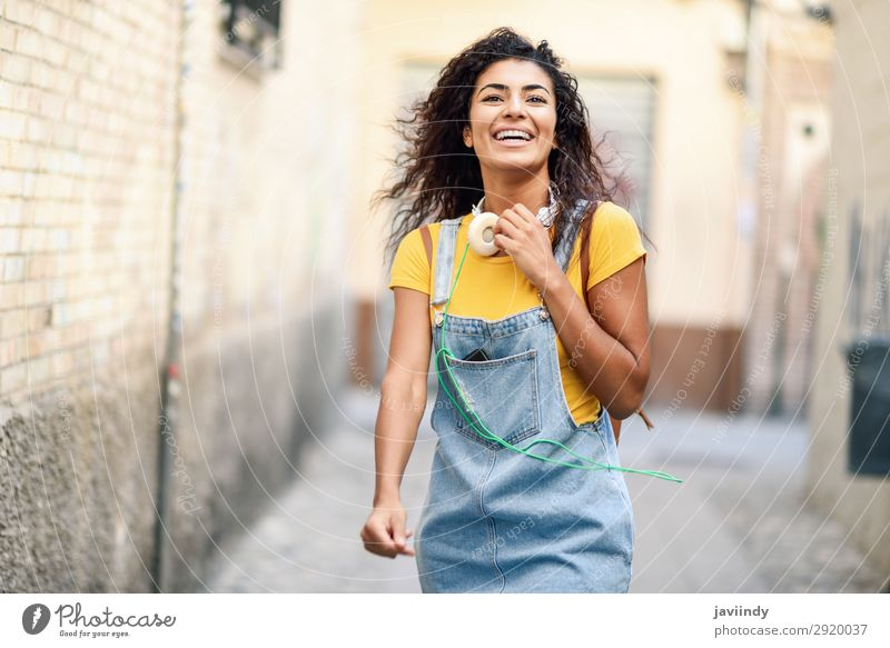 Young African woman with headphones walking outdoors Lifestyle Style Joy Happy Beautiful Hair and hairstyles Human being Feminine Young woman