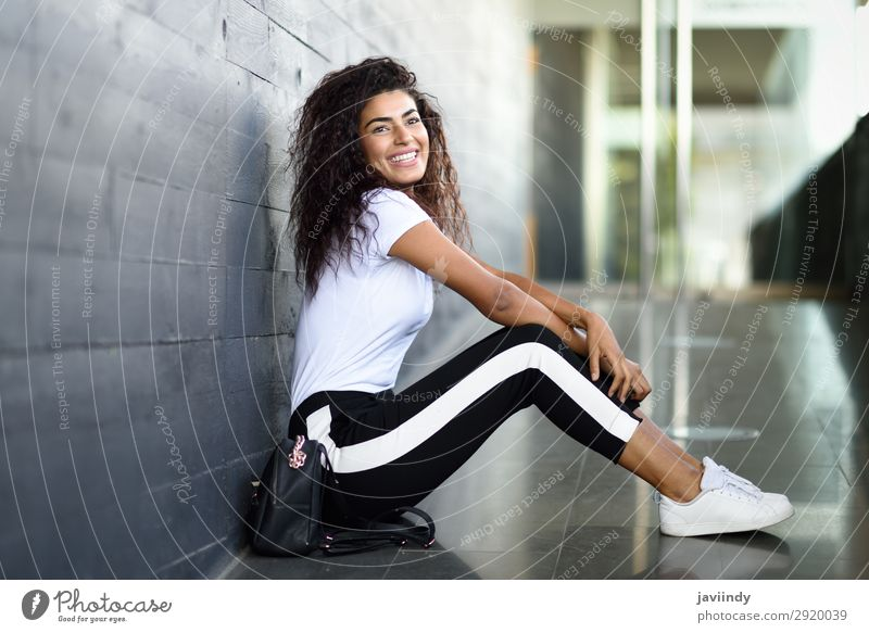 Happy Arab woman, black curly hairstyle sitting on urban floor. Lifestyle Style Beautiful Hair and hairstyles Face Sports Human being Feminine Young woman