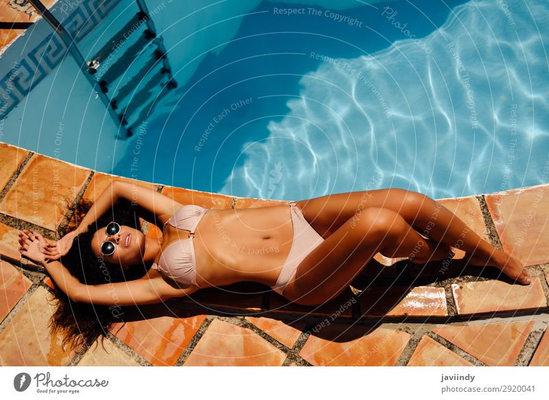 Relaxed woman sunbathing on the edge of a swimming pool Lifestyle Happy Beautiful Body Hair and hairstyles Skin Relaxation Swimming pool Leisure and hobbies