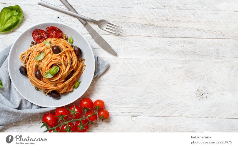 Spaghetti with tomato sauce olives and capers Vegetable Lunch Dinner Vegetarian diet Plate Fork Wood Above Green Red Tradition pasta puttanesca Olive Basil