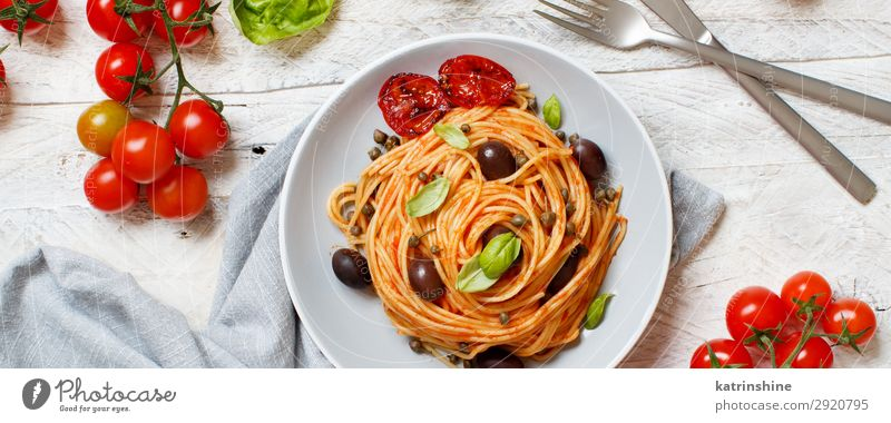 Spaghetti with tomato sauce olives and capers Vegetable Lunch Dinner Vegetarian diet Plate Fork Spoon Wood Above Green Red Tradition pasta puttanesca Olive