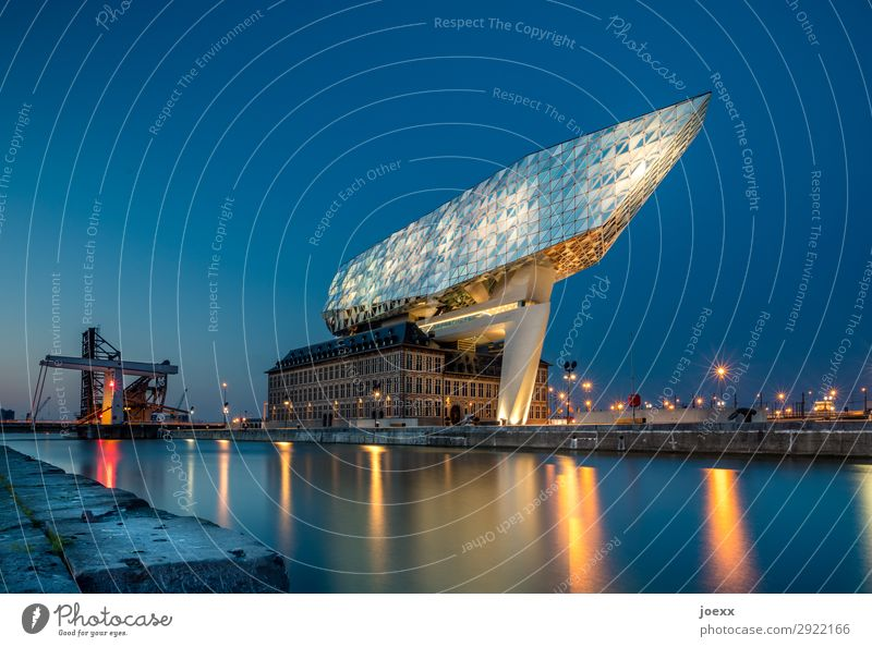 Futuristic building on the waterfront with glass facade illuminated in the evening Modern architecture Zaha Hadid The Port House futuristic Glas facade Facade