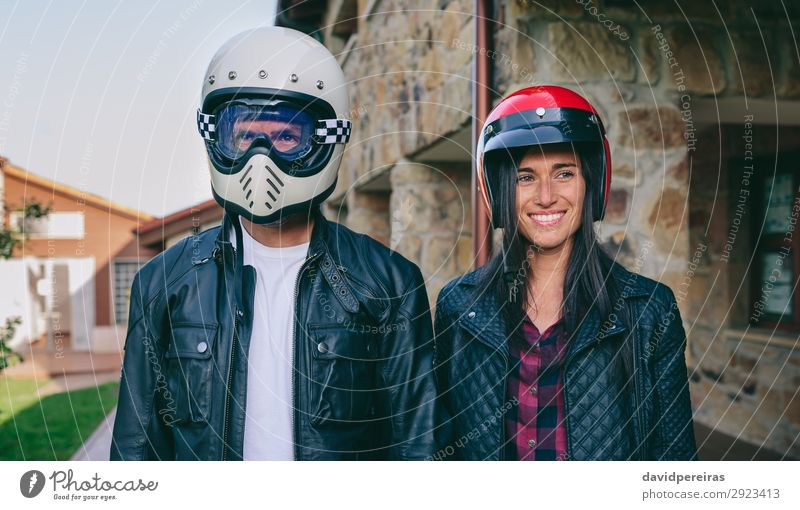 Couple posing with motorcycle helmets Lifestyle Happy Beautiful House (Residential Structure) Human being Woman Adults Man Grass Fashion Smiling Authentic Funny