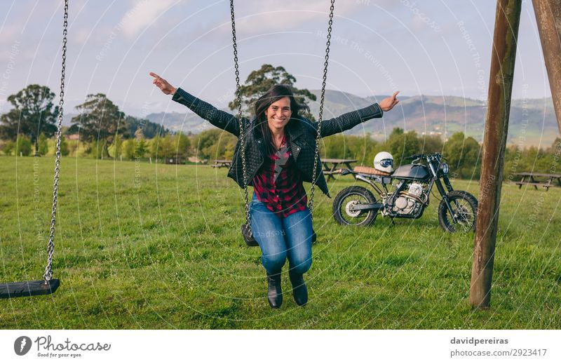Young woman swinging with motorcycle in the background Lifestyle Happy Beautiful Freedom Human being Woman Adults Nature Tree Grass Park Meadow Vehicle