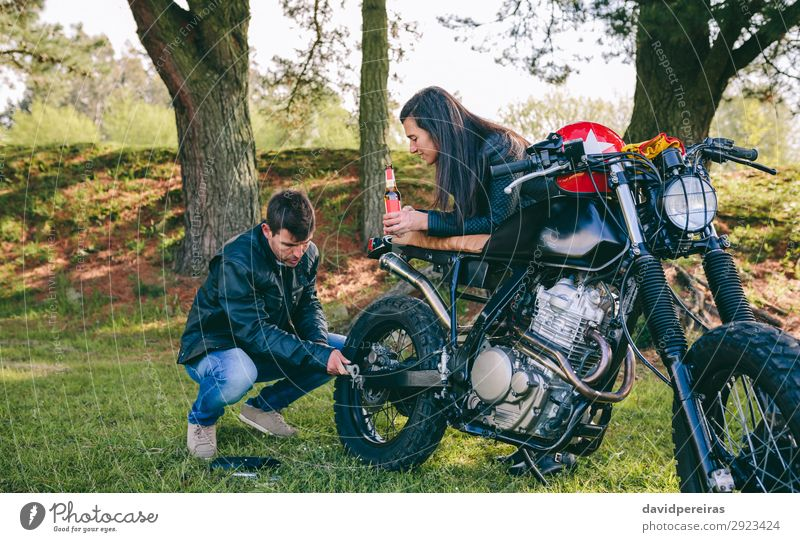 Man fixing his motorcycle while his girlfriend looks at him Drinking Cold drink Alcoholic drinks Beer Lifestyle Vacation & Travel Trip To talk Human being Woman