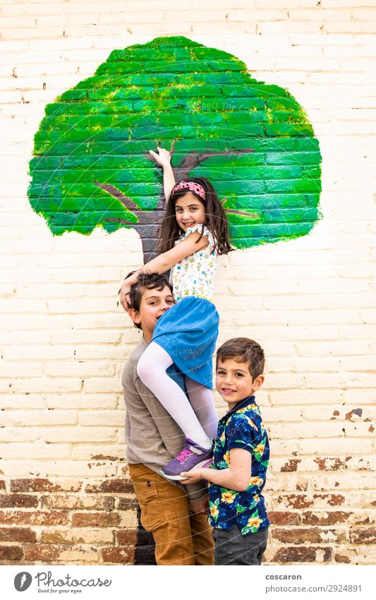 Three kids playing with a tree painted on a wall Child Human being Vacation & Travel Nature Summer Blue Town Beautiful Green Tree House (Residential Structure)