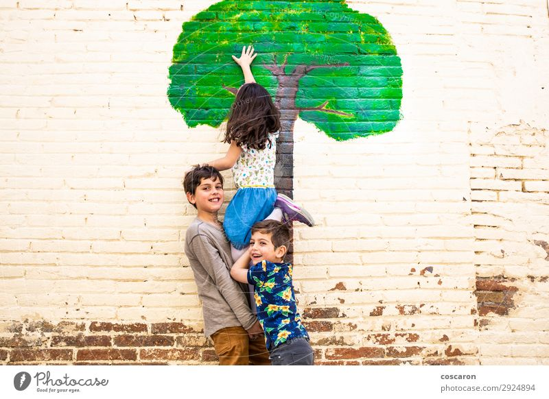 Three kids playing with a tree painted on a wall Child Human being Vacation & Travel Nature Youth (Young adults) Summer Blue Town Beautiful Green Tree Joy