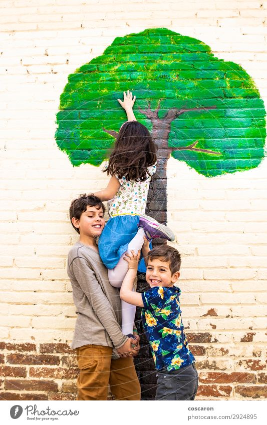 Three kids playing with a tree painted on a wall Joy Happy Beautiful Leisure and hobbies Playing Freedom Summer Garden Climbing Mountaineering Child School