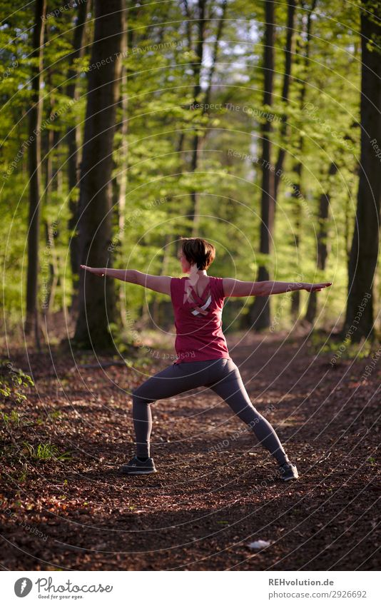 Woman doing yoga in the forest Central perspective Shallow depth of field blurriness Sunlight Silhouette Evening Day Exterior shot Colour photo