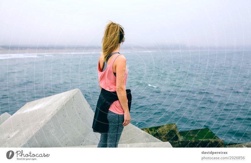 Unrecognizable young woman watching the sea Lifestyle Wellness Relaxation Calm Ocean Sports Human being Woman Adults Fog Concrete Observe Fitness Athletic