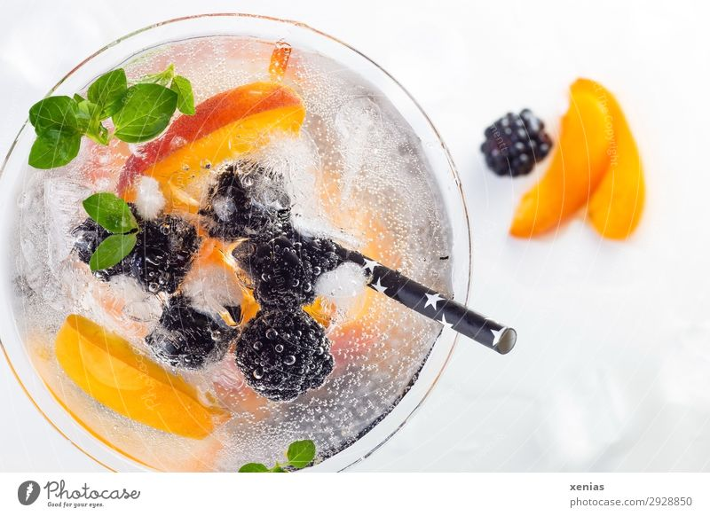 Delicious iced soft drink with blackberry and nectarine, decorated with oregano and a black drinking straw Beverage Cold drink fruit Nectarine Herbs and spices