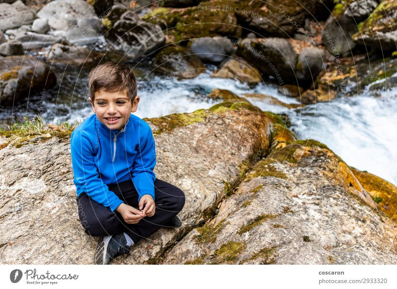 Cute litle boy sitting near of a wild river Child Human being Vacation & Travel Nature Man Summer Blue Beautiful Water White Joy Mountain Lifestyle Adults