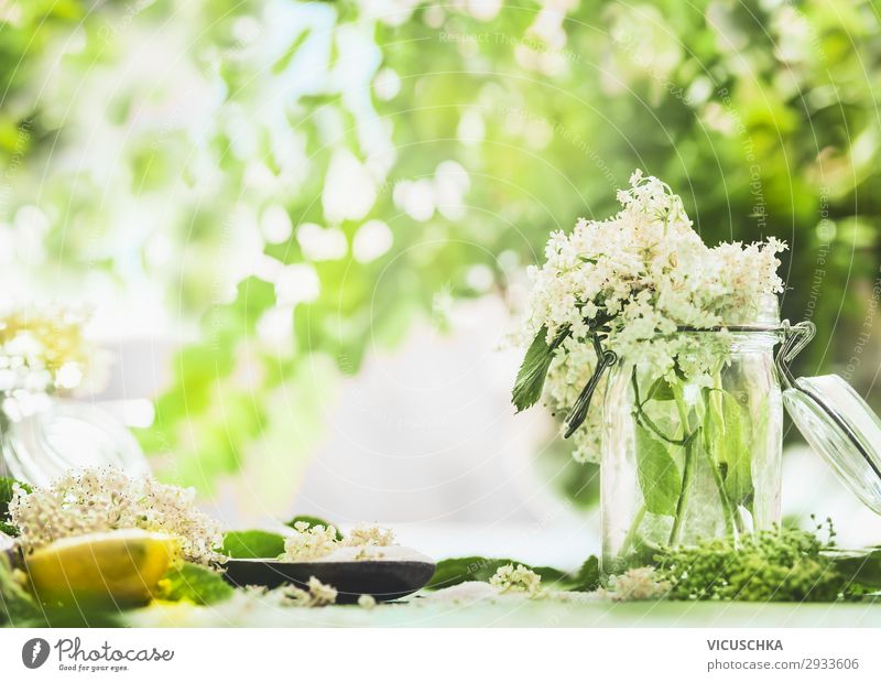 Elderberry blossoms in glass on kitchen table with lemon and sugar. Food Nutrition Organic produce Beverage Juice Crockery Style Design Healthy Healthy Eating