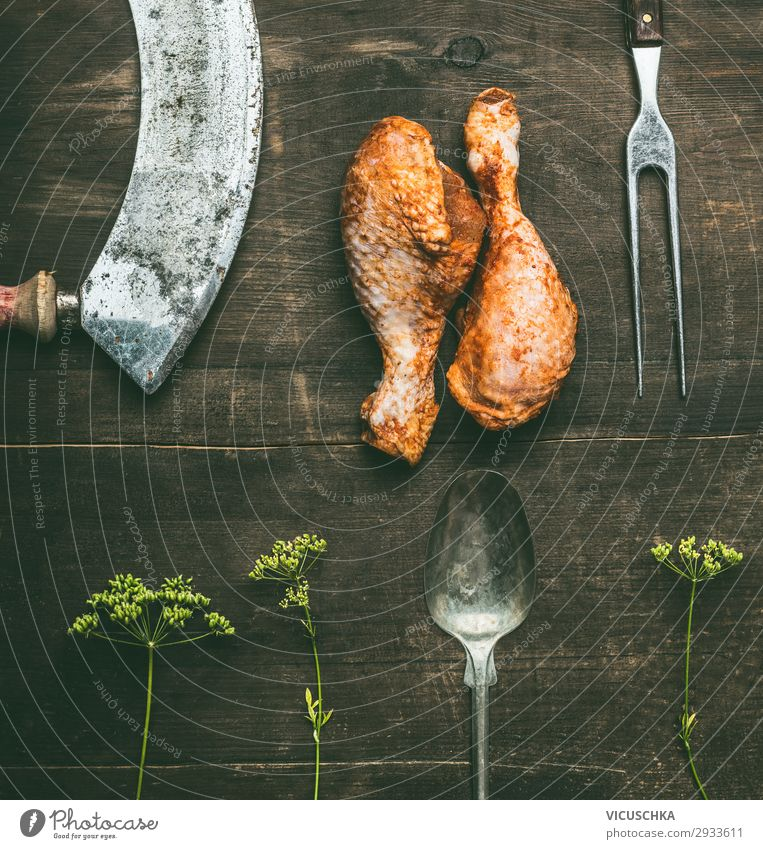 Raw barbecue marinated chicken drumstick with fresh herbs and kitchen utensils on rustic wooden background, top view. Grill preparation raw grill steakhouse