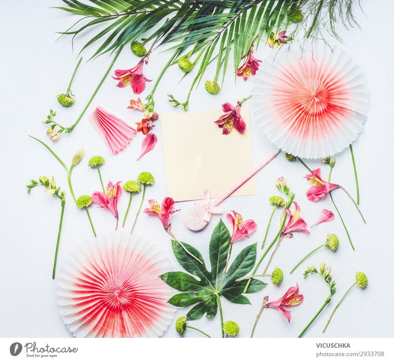 Blank greeting card mock up with paper party fans, tropical leaves and exotic flowers on white background, top view. Flat lay. Frame. Copy space for your text or design
