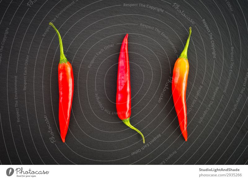 Red hot chili peppers on dark background Vegetable Herbs and spices Eating Vegetarian diet Healthy Eating Dark Simple Fresh Hot Cold Natural Green Black Colour