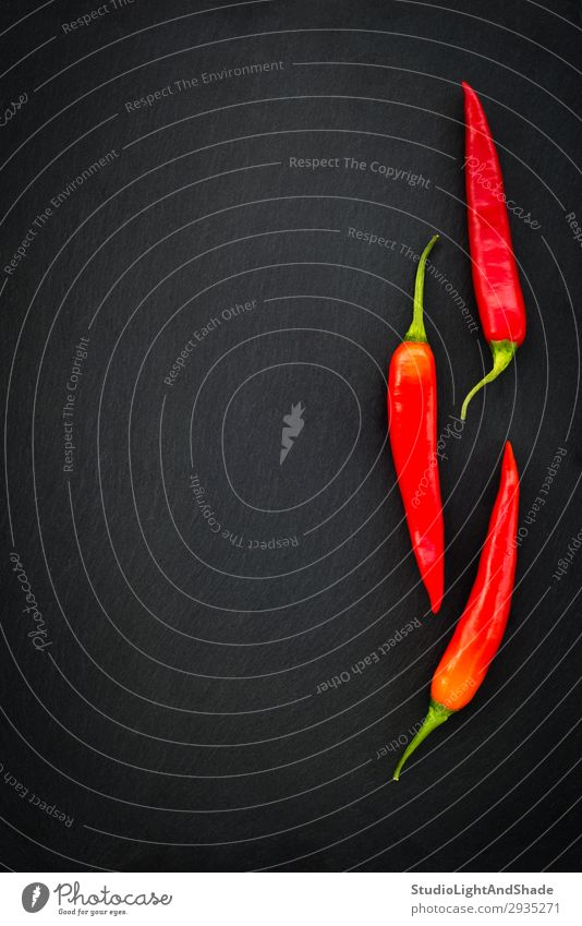 Three red chili peppers on dark background Vegetable Herbs and spices Eating Vegetarian diet Healthy Eating Dark Simple Fresh Hot Cold Natural Green Red Black