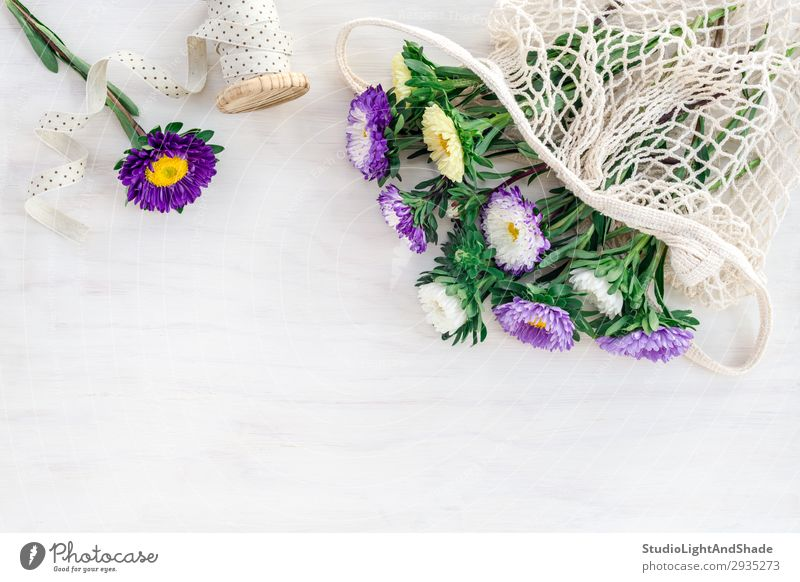 Asters in a mesh bag on white wooden background Nature Summer Plant Blue Colour Beautiful Green White Flower Joy Food Blossom Natural Garden Copy Space Design