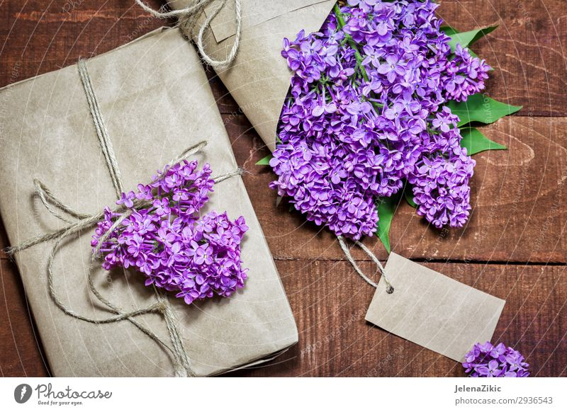 Gift and bouquet of lilacs on a wooden table Beautiful Summer Decoration Desk Table Feasts & Celebrations Mother's Day Easter Wedding Birthday Craft (trade)