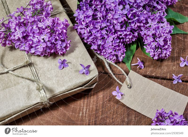 Gift and bouquet of lilacs on a wooden table Beautiful Summer Decoration Desk Table Feasts & Celebrations Valentine's Day Mother's Day Easter Christmas & Advent