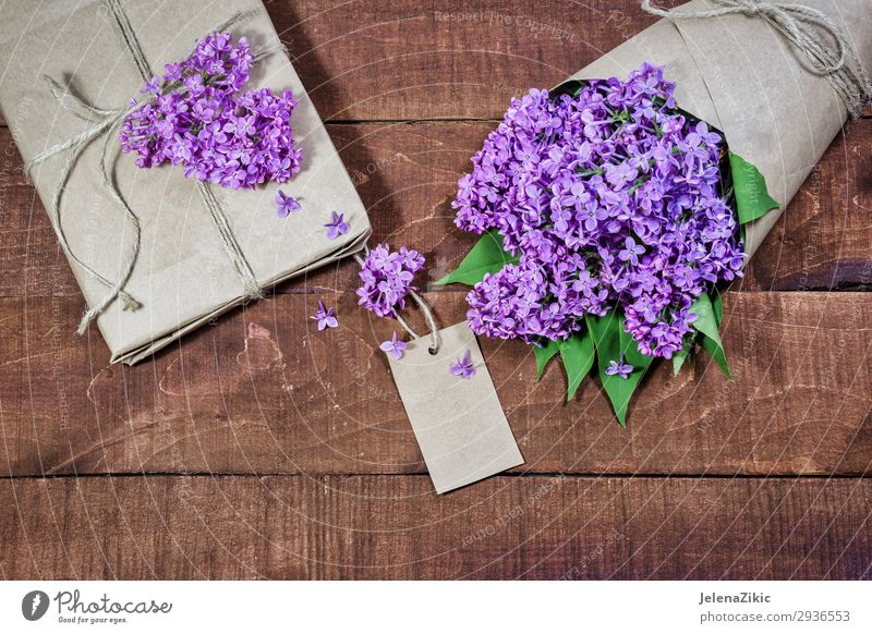 Gift and bouquet of lilacs on a wooden table Beautiful Summer Decoration Desk Table Feasts & Celebrations Valentine's Day Mother's Day Easter Wedding Birthday