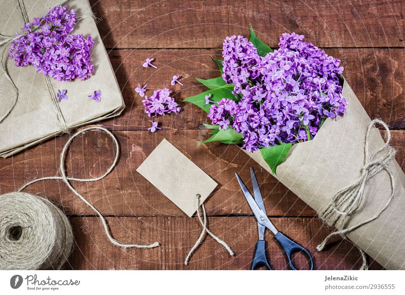 Gift and bouquet of lilacs on a wooden table Old Beautiful Flower Adults Wood Love Blossom Spring Natural Feasts & Celebrations Decoration Birthday Table Paper