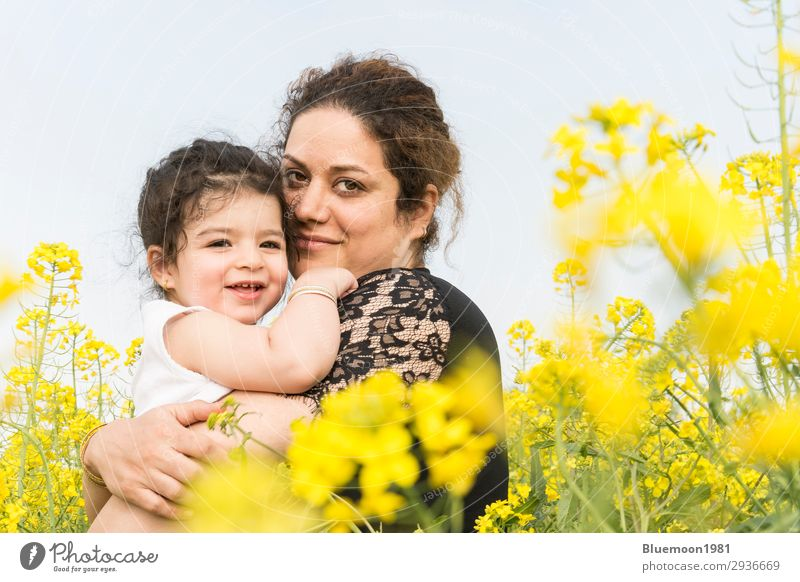 Happy mother embraced her cute little girl at canola field Woman Child Human being Sky Vacation & Travel Nature Youth (Young adults) Young woman Summer Plant