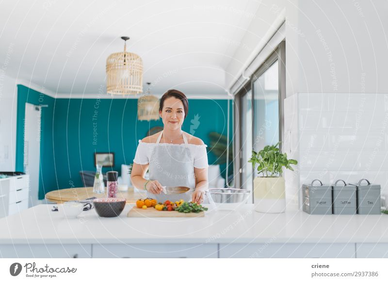 Smiling young female adult cutting vegetables in kitchen Vegetable Kitchen Woman Adults preparing food healthy indoor Home cooking chef Ingredients Tomato knife