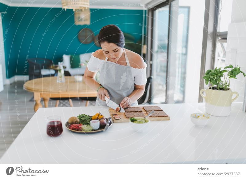 Woman preparing sandwiches in kitchen Vegetable Bread Kitchen Adults Smiling food healthy indoor Home cooking chef Ingredients Tomato knife cutting toast