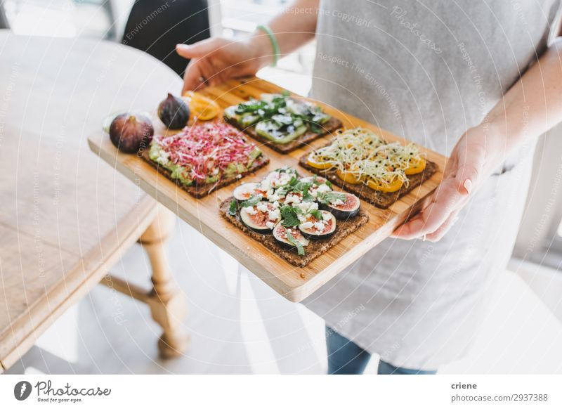Woman carying wooden board with healthy sandwiches Cheese Fruit Bread Breakfast Lunch Hand Joy toast Sandwich herbs Fig food Apron cooking chef Snack Dish feta