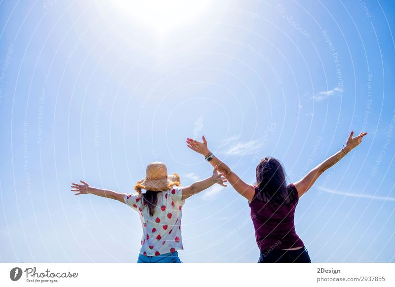 Two young woman sitting on a fence arms raised against blue sky Lifestyle Joy Happy Beautiful Relaxation Leisure and hobbies Vacation & Travel Freedom Summer