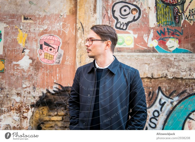 Portrait of a young man in front of a wall Italy Rome Wall (building) Portrait photograph Young man Street art Coat Profile Look back Looking