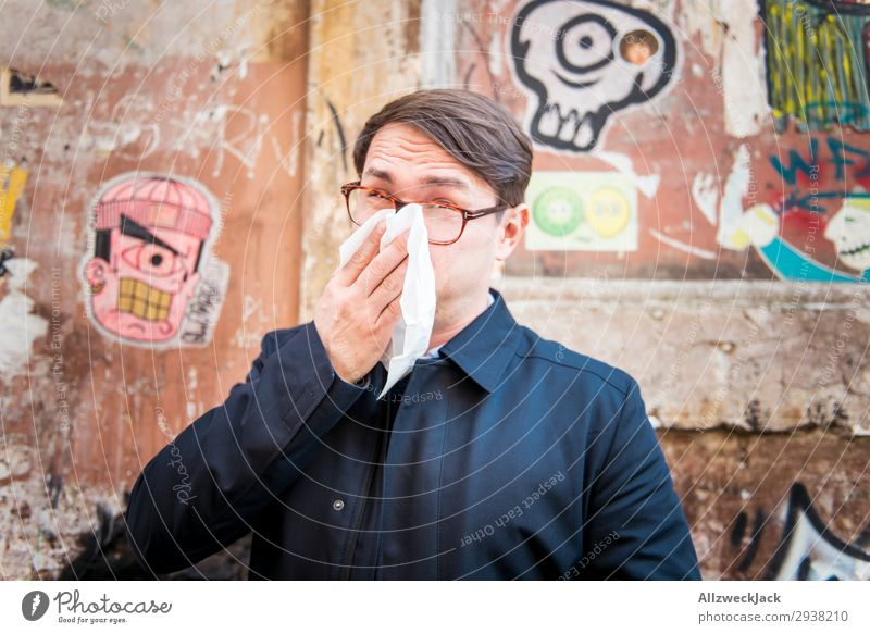 young man is ill and wipes his nose Wall (building) Portrait photograph Young man Close-up Face Common cold Illness Blow one's nose Handkerchief Breathe Coat