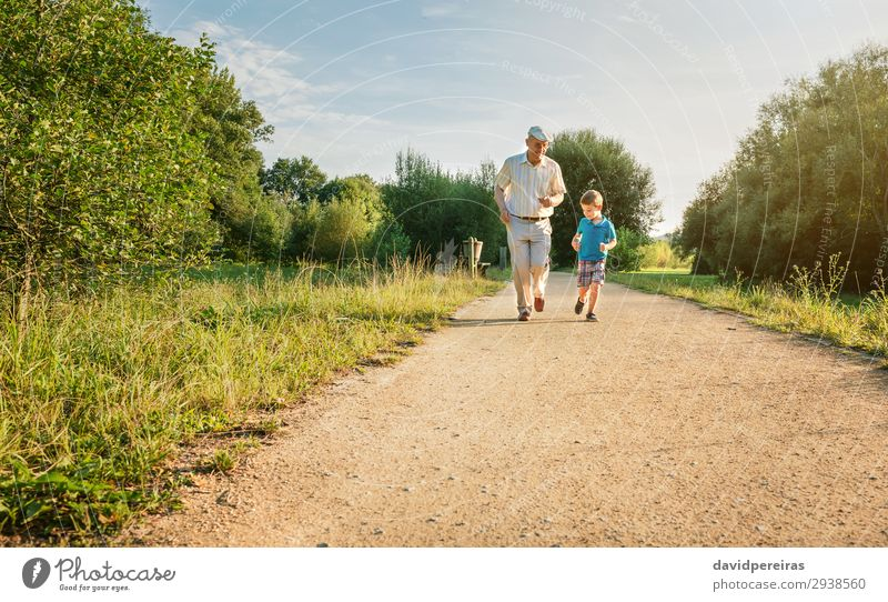 Senior man and happy child running outdoors Child Human being Nature Man Old Summer Tree Joy Adults Love Family & Relations Happy Boy (child) Copy Space Playing