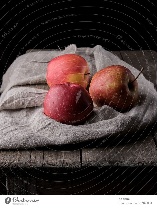 three fresh red apples lay on gray linen napkin Fruit Apple Dessert Nutrition Vegetarian diet Diet Table Nature Plant Autumn Wood Fresh Natural Juicy Gray Red