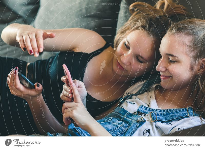 Young women using mobile phones watching music clip Woman Summer Lifestyle Adults To talk Together Friendship Modern Technology Sit To enjoy Authentic Observe