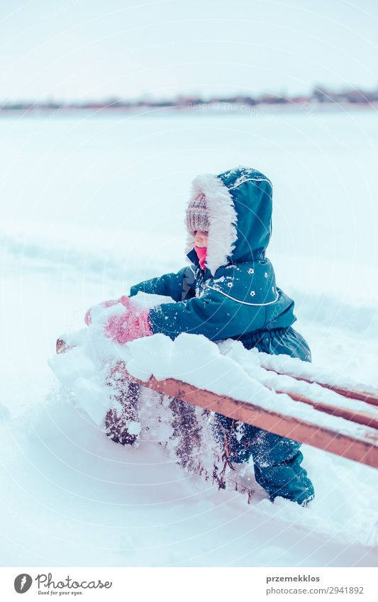 Little girl enjoying winter removing snow from a bench Lifestyle Joy Happy Playing Winter Snow Child Human being Woman Adults Infancy 1 Nature Landscape
