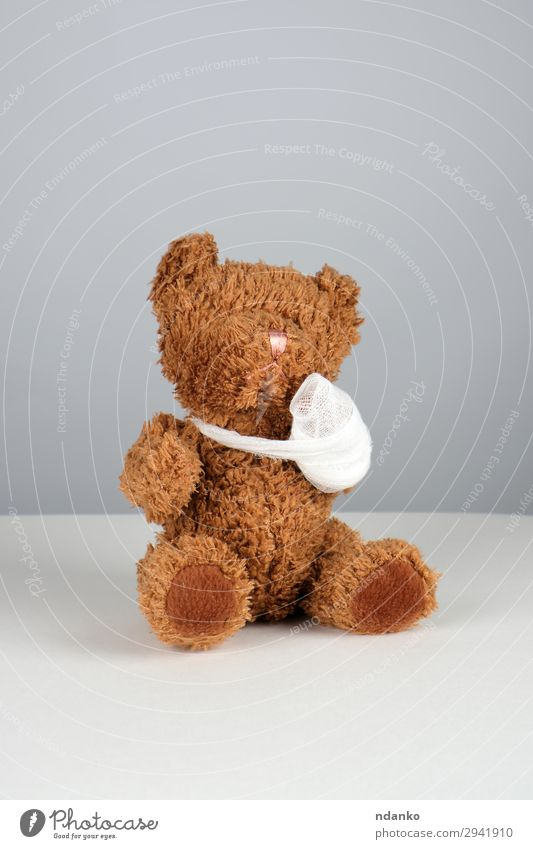 brown teddy bear with a bandaged paw Medical treatment Illness Medication Child Hospital Infancy Arm Band Toys Teddy bear Sit Small Funny Cute Brown White Pain