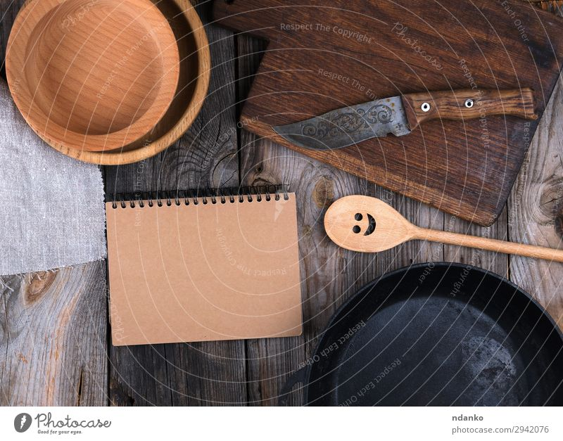 empty black round frying pan, cutting board Plate Pan Knives Spoon Table Kitchen Paper Wood Metal Old Above Clean Brown Gray Black background Cast cooking