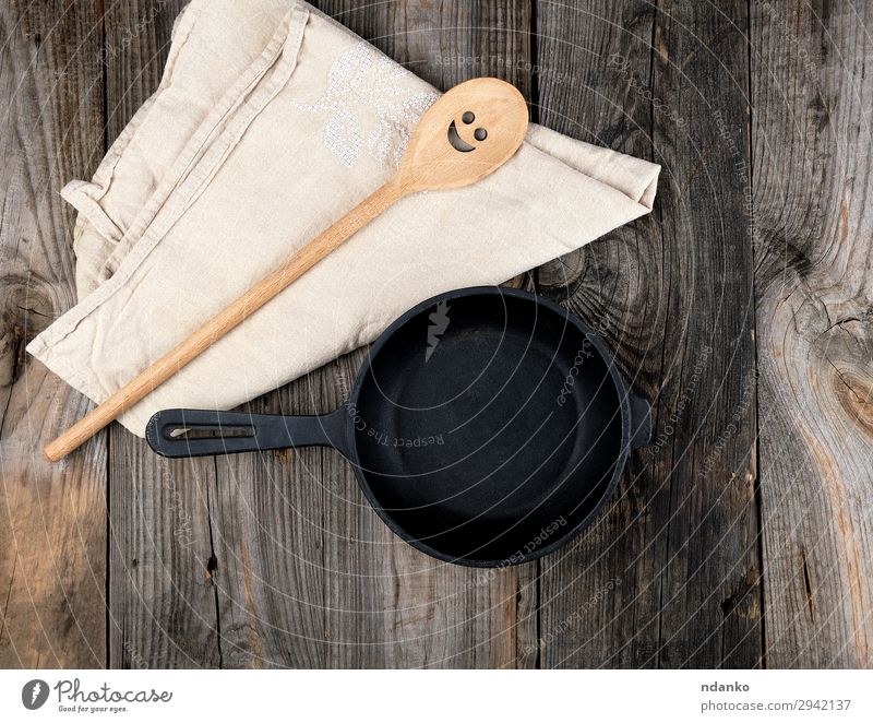 empty black round frying pan Pan Spoon Table Kitchen Tool Wood Metal Old Above Clean Brown Gray Black background board Cast cooking cookware Culinary dishware