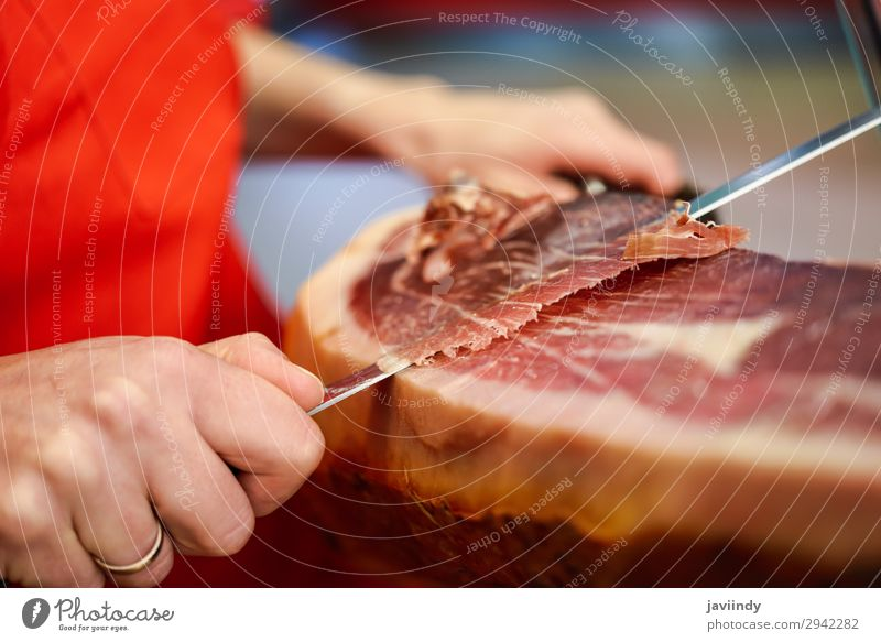 Cutter carving slices from a whole bone-in serrano ham Food Meat Shopping Restaurant Work and employment Profession Business Human being Woman Adults 1