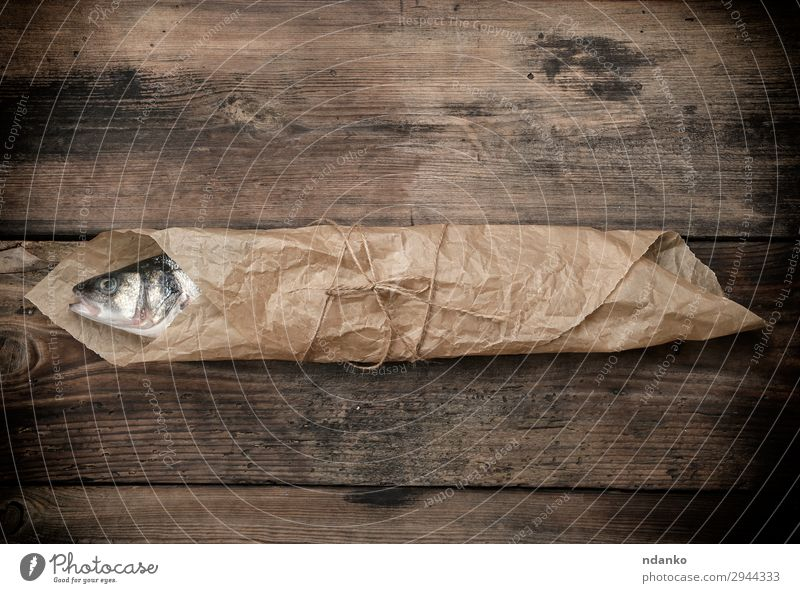 sea bass fish wrapped in a brown paper Seafood Nutrition Ocean Table Kitchen Rope Animal Paper Wood Eating Fresh Above Brown Gray bag board cooking labrax one