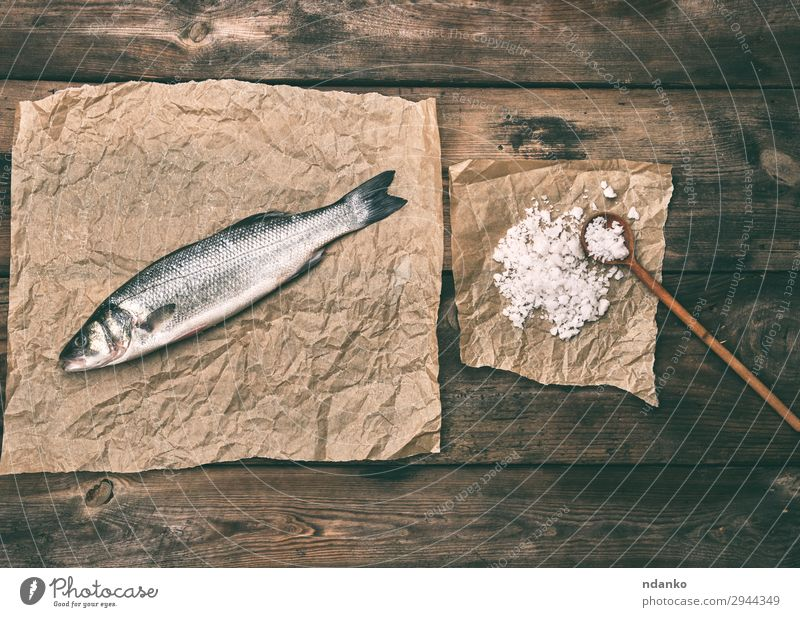 sea bass fish on brown crumpled paper Fish Seafood Nutrition Spoon Ocean Kitchen Animal Paper Wood Fresh Above Brown Gray salt board cooking labrax one Raw