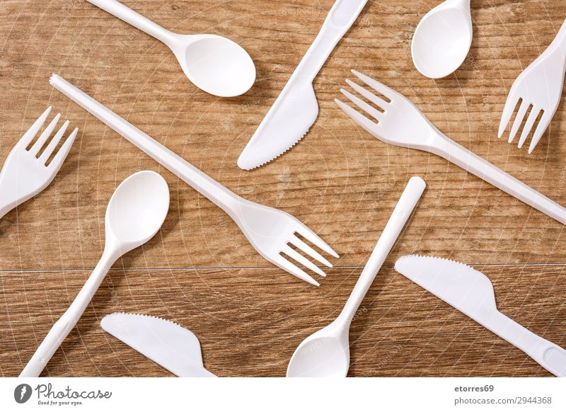 Disposable plastic cutlery on wooden table. Top view Kitchen Plastic Table Crockery Recycling empty Environment Fork garbage Group Industrial Birthday knife