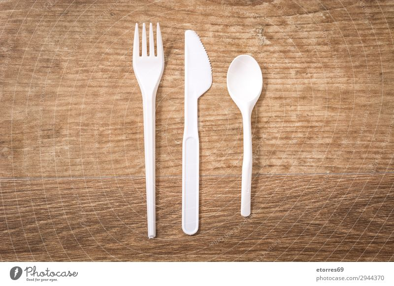 Disposable plastic cutlery on wooden table. Top view Kitchen Plastic tableware Crockery Recycling empty Environment Fork garbage Group Industrial Birthday