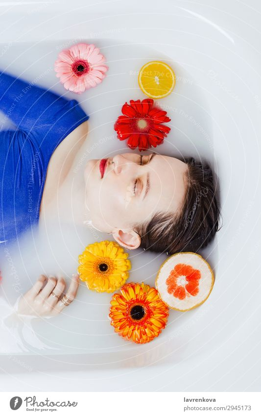 Woman lying in bathtub filled with flowers and fruits Swimming & Bathing Bathroom Bathtub Beautiful Beauty Photography Flower Blue Citrus fruits Decoration
