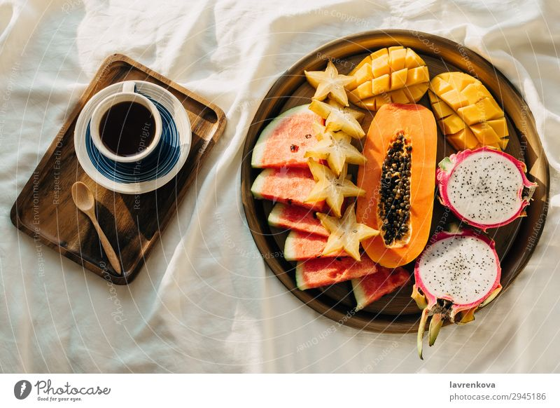 Coffee or tea and tropical fruit plat on white bed Bedroom Beverage Breakfast Carambole Cup Dragonfruit Exotic flatlay Healthy Eating Mango Morning Mug Notebook