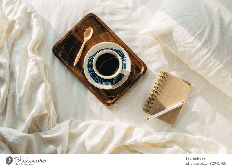 Coffee on wooden tray with notebook and pen on bed flatlay Tray Wood Spoon Tea Bedroom sheets Pillow Pen Hot Paper Notebook Cup Mug Vantage point Top Brown