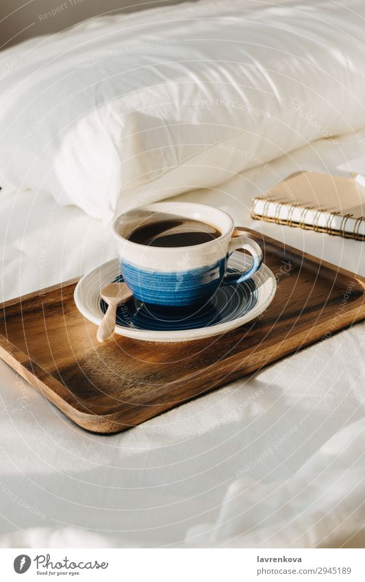 Coffee on wooden tray with notebook and pen on bed background Bedroom Beverage Breakfast Brown Cup Hot Morning Mug Notebook Paper Pen Pillow Sheet Spoon Table